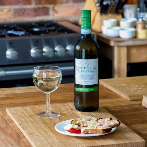 Green Wine Bottle Beside Wine Glass on Brown Wooden Table