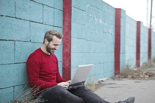 Man Leaning Against Wall Using Laptop