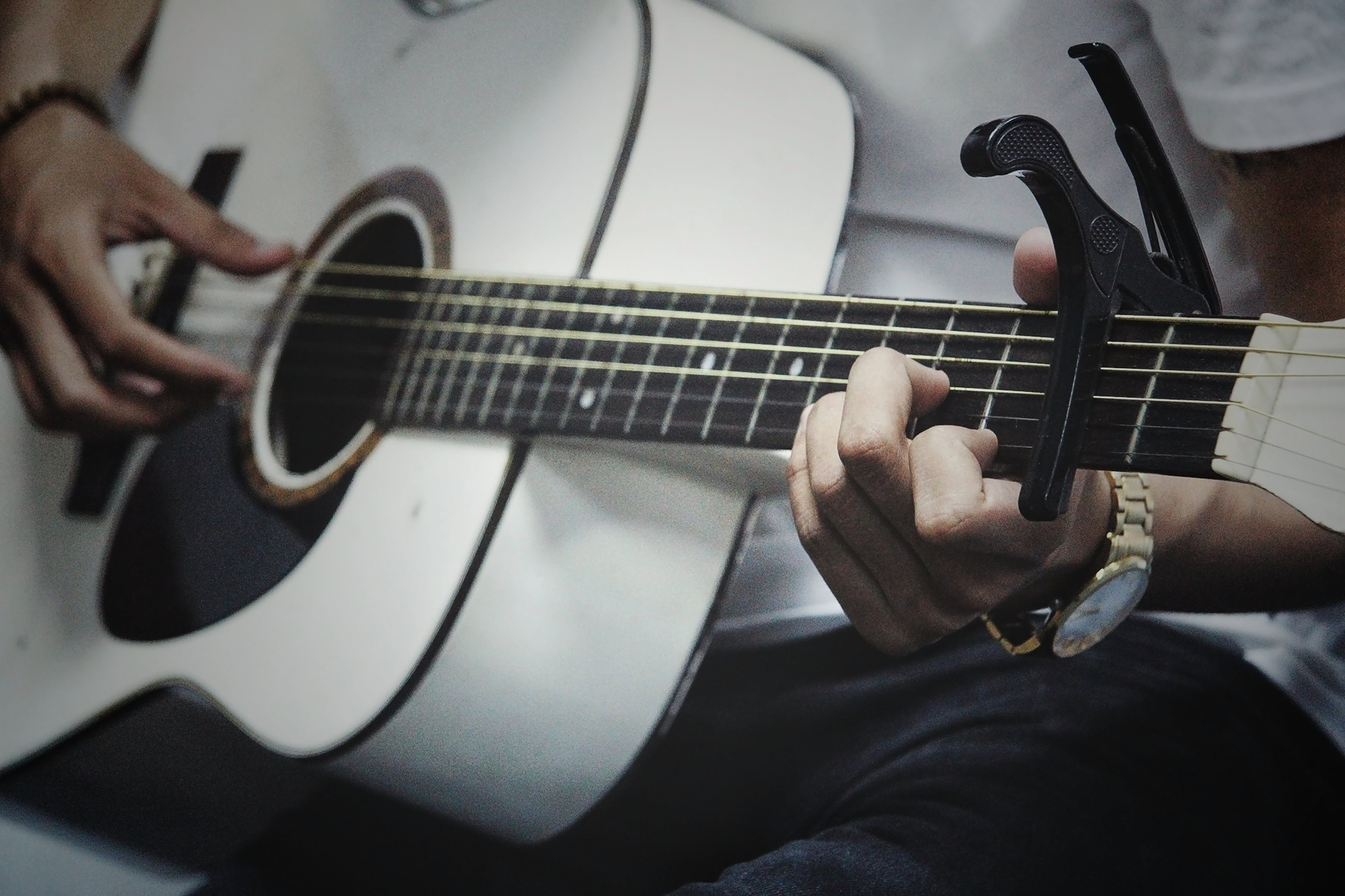 Man Holding a White Dreadnought Acoustic Guitar