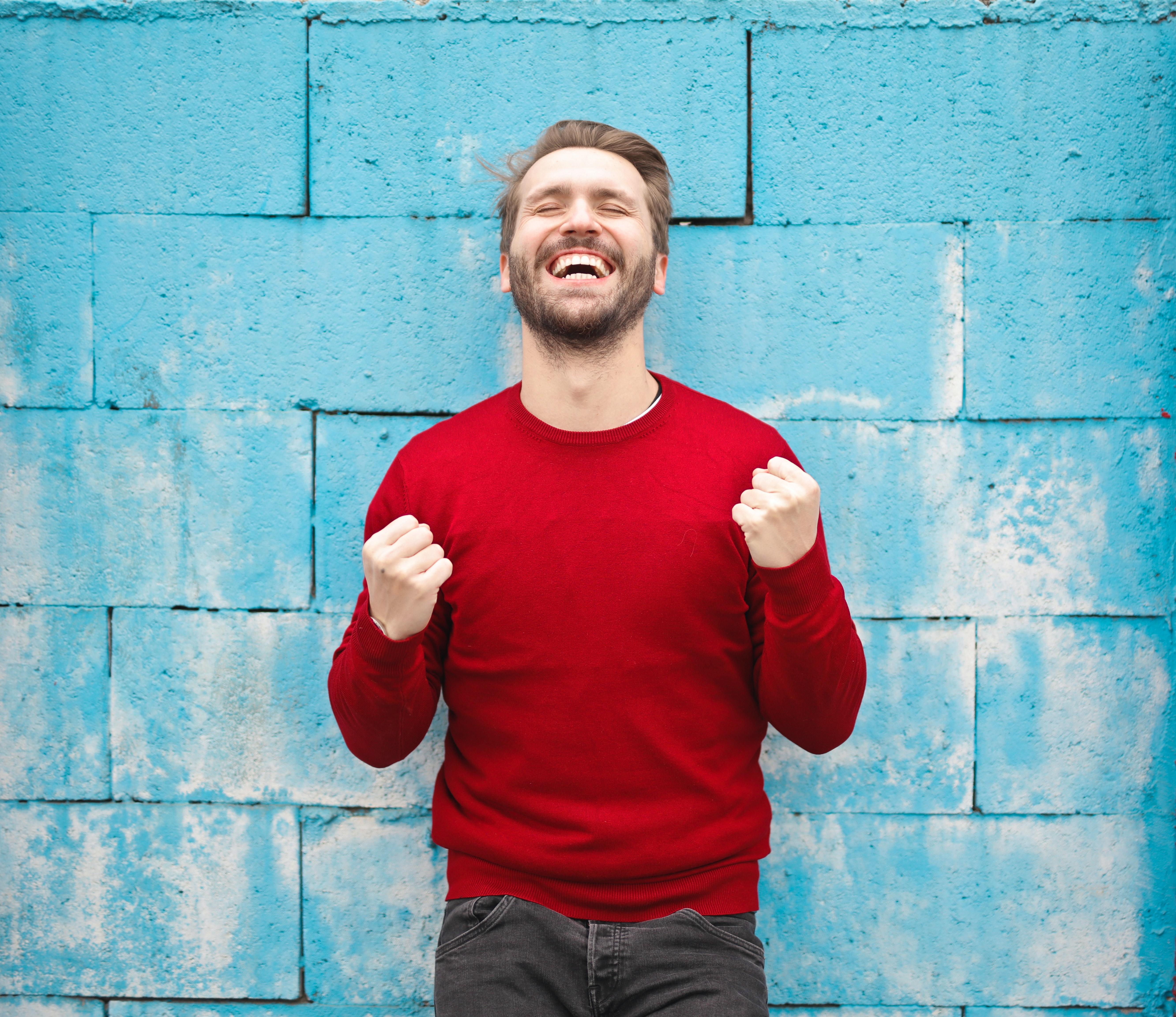 A happy man wearing red crew-neck sweatshirt.   Photo: Pexels