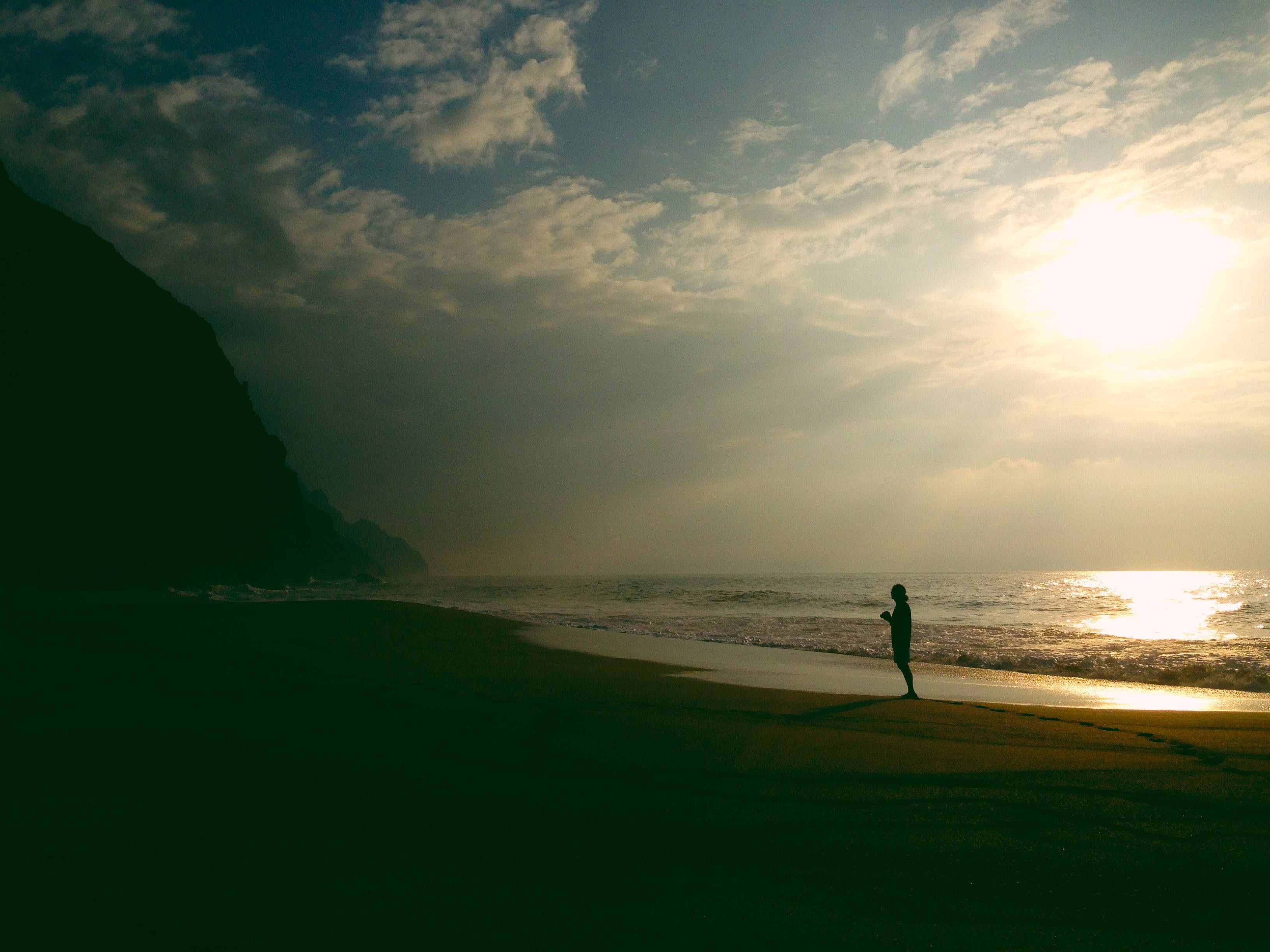 Silhouette Photography of Person Standing on Stand Beside Seashore during Sunset
