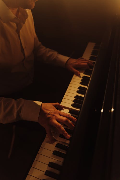 Person in White Long Sleeve Shirt Playing Piano