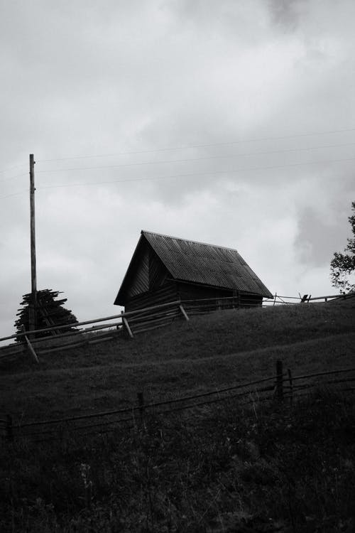 Grayscale Photo of Wooden House Near Electric Post