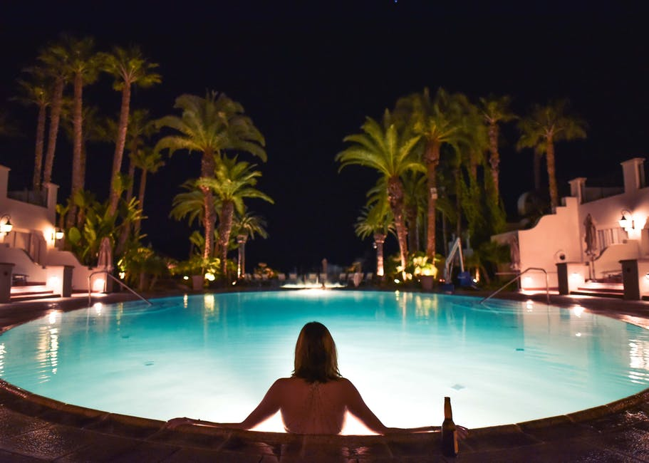 Topless Woman In Pool Facing Trees During Night Time