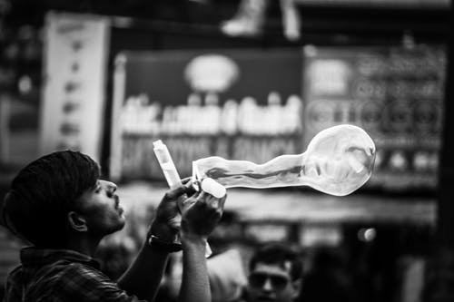 Man Playing Bubbles Grayscale Photo