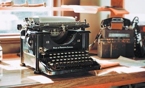 Классическая черная пишущая машинка на коричневом деревянном столе