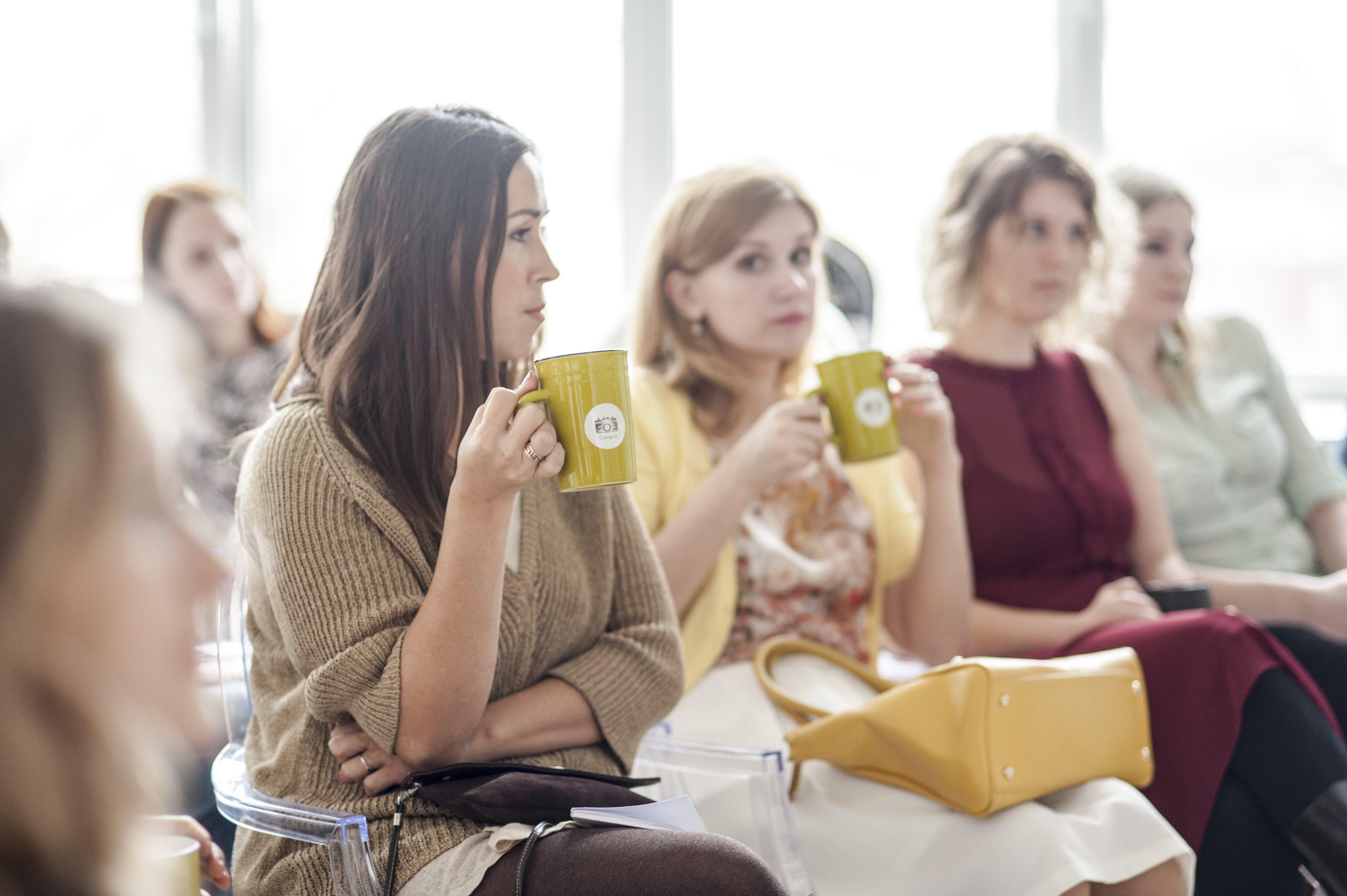 Woman Wearing Brown Corduroy Coat Holding Mug While Sitting on Chair