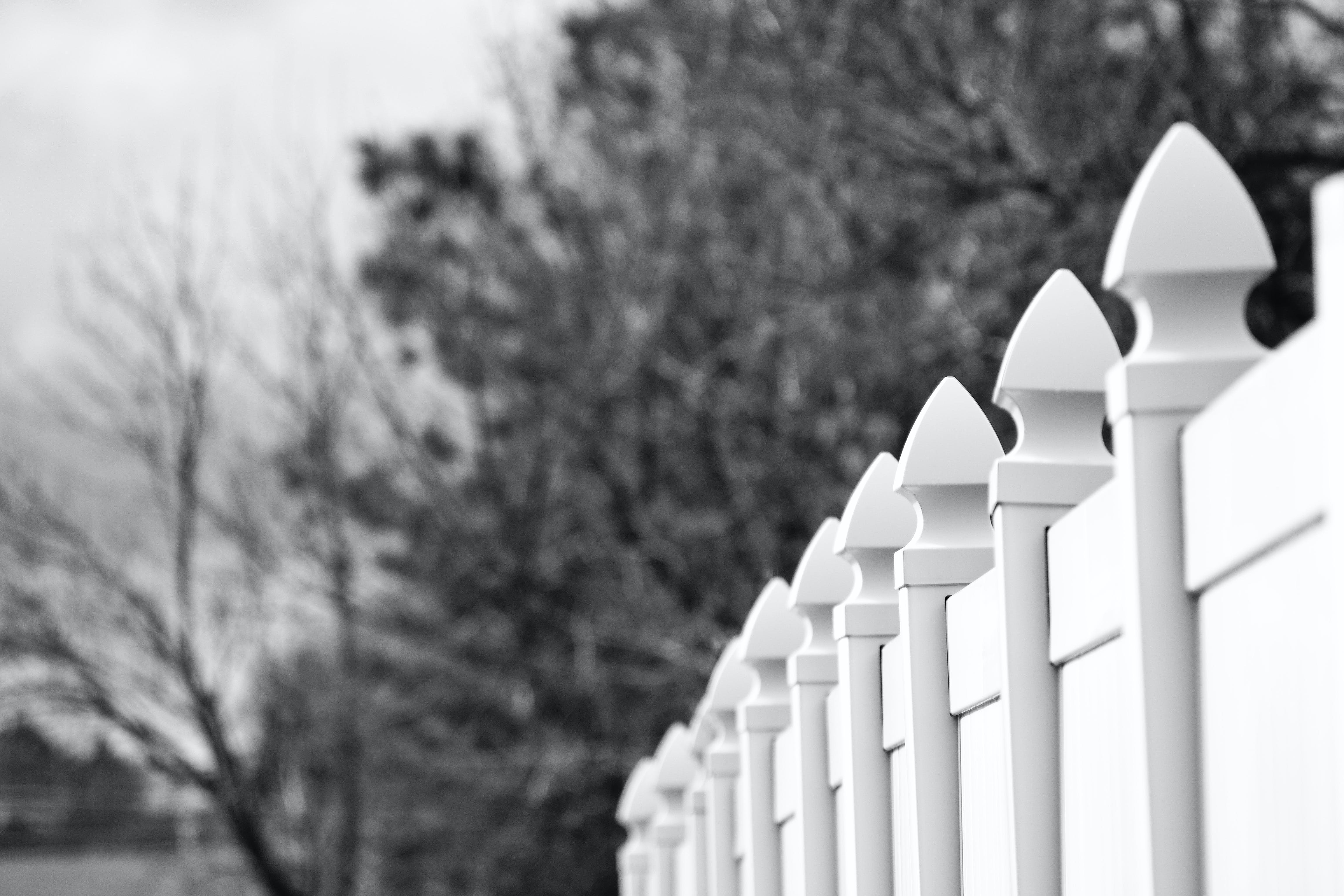 Gray Scale Photo of White Fence