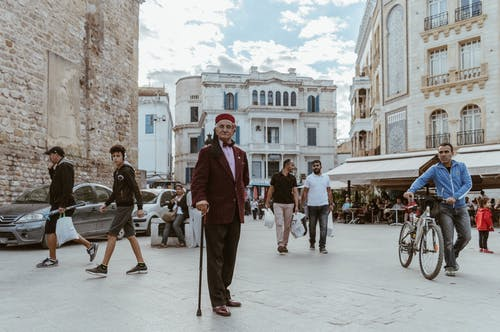 Man in Red Blazer Walking on Sidewalk