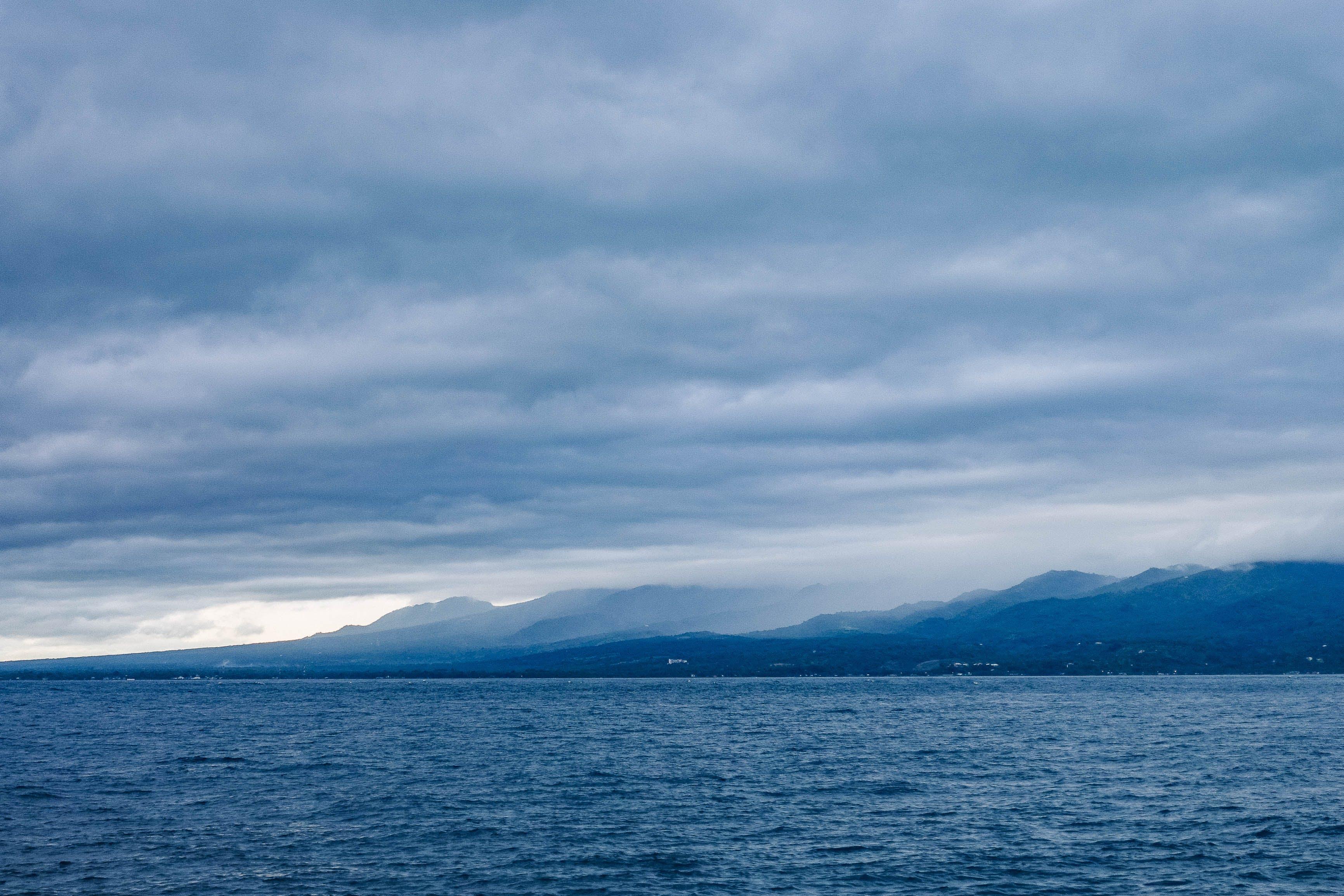Island Across Body of Water Under Cloudy Sky