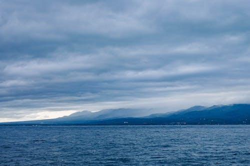 Ingyenes stockfotó felhők, hegyek, hullámok, napfény témában