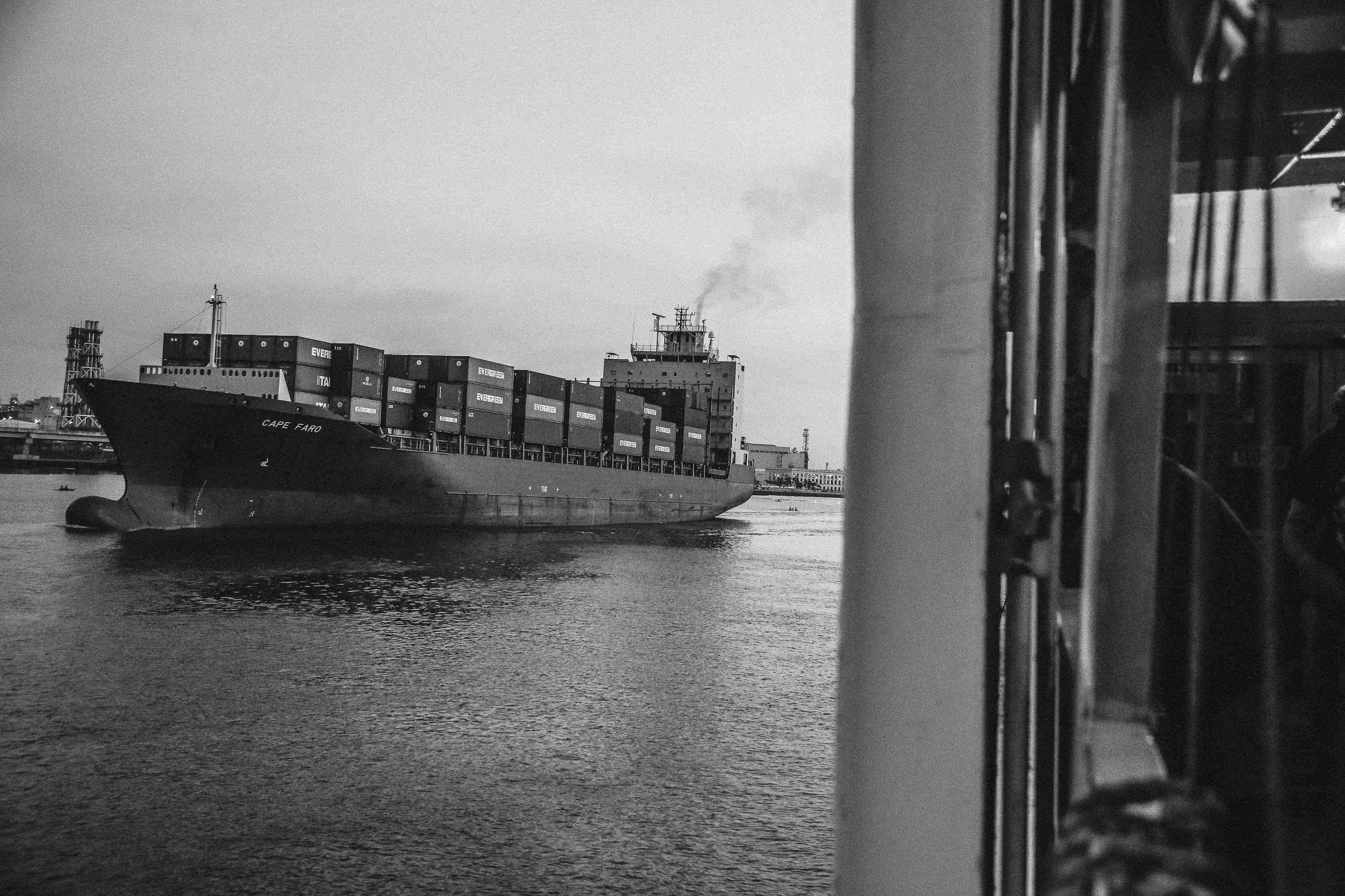Greyscale Photo of Cargo Ship on Ocean