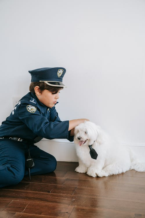 A Boy in a Police Costume Playing with His Dog