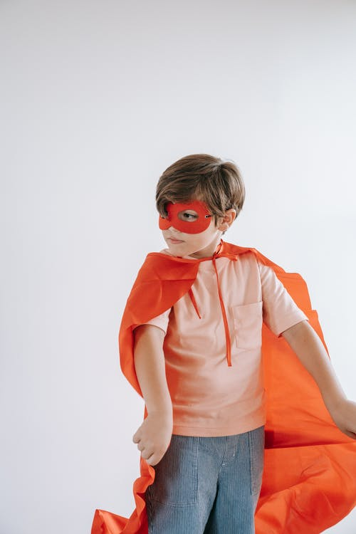 A Boy Wearing a Cape and a Mask