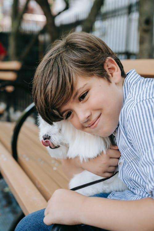 Boy Hugging White Furry Animal