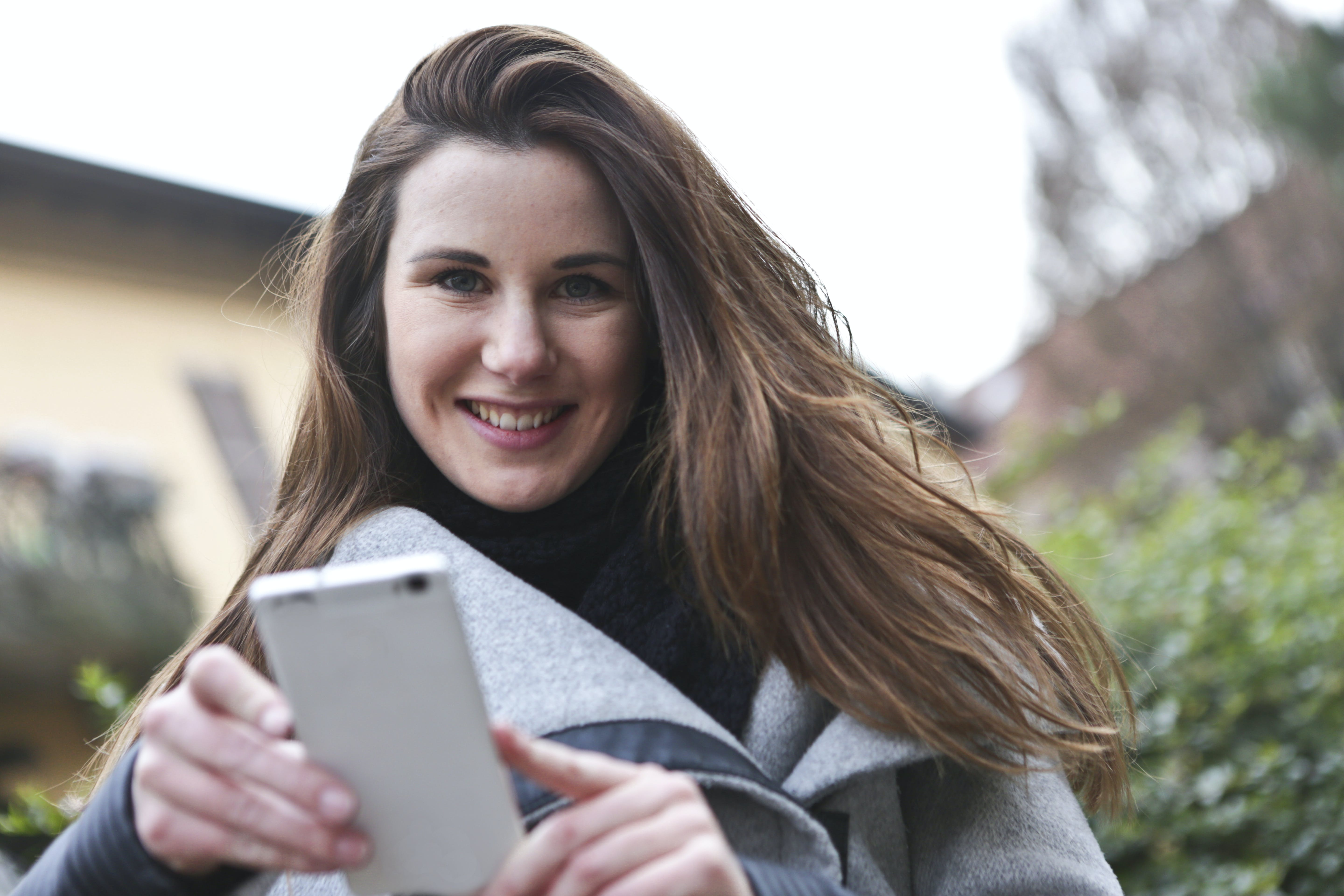 Woman in Gray Coat Holding White Smartphone