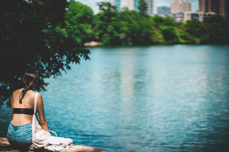 Woman in Black Top Sitting Beside Body of Water