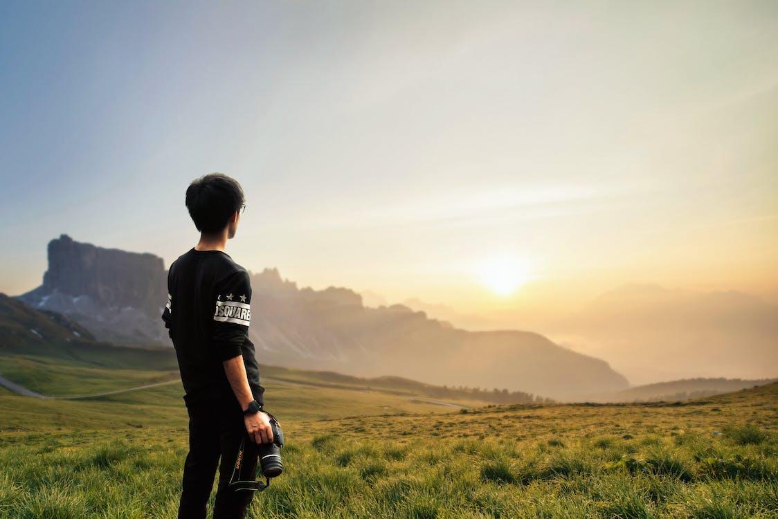 Sepia Photography of Man Wearing Black Sweatshirt Holding Camera