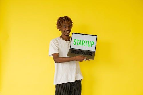 Gratis arkivbilde med afrikansk-amerikansk, bærbar datamaskin, gul bakgrunn