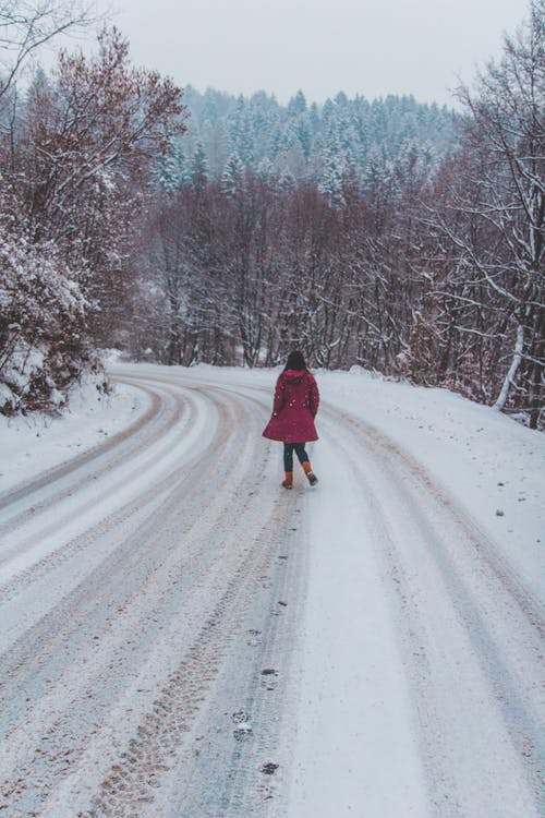 Woman Wearing Red Coat Standing on White Snow Road