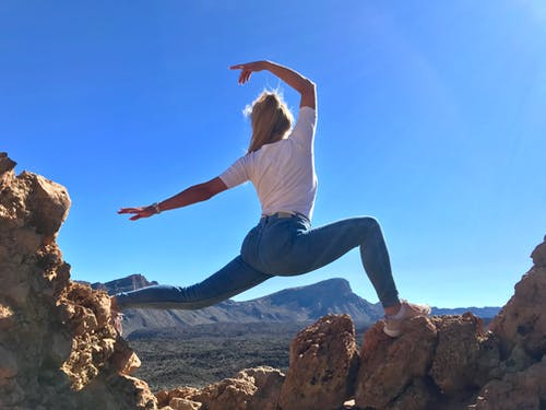 Woman in White T-shirt and Blue Jeans Doing Yoga on Rock Formation