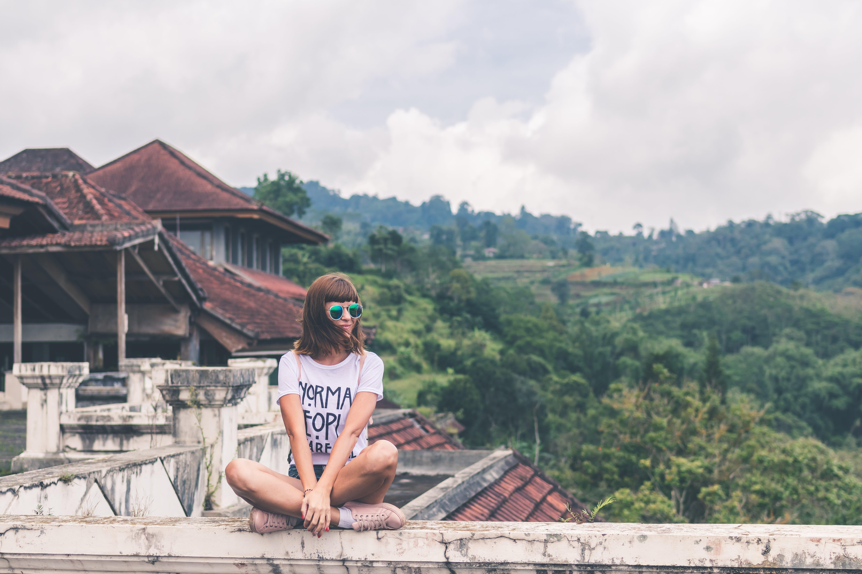 Photo of Woman Sitting on Concrete Balustrade