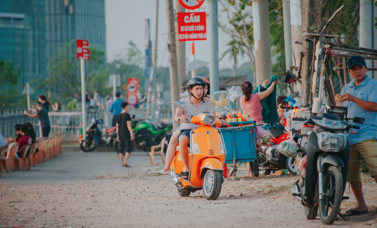 Man Wearing Grey Shirt Riding on Orange Motor Scooter at Daytime