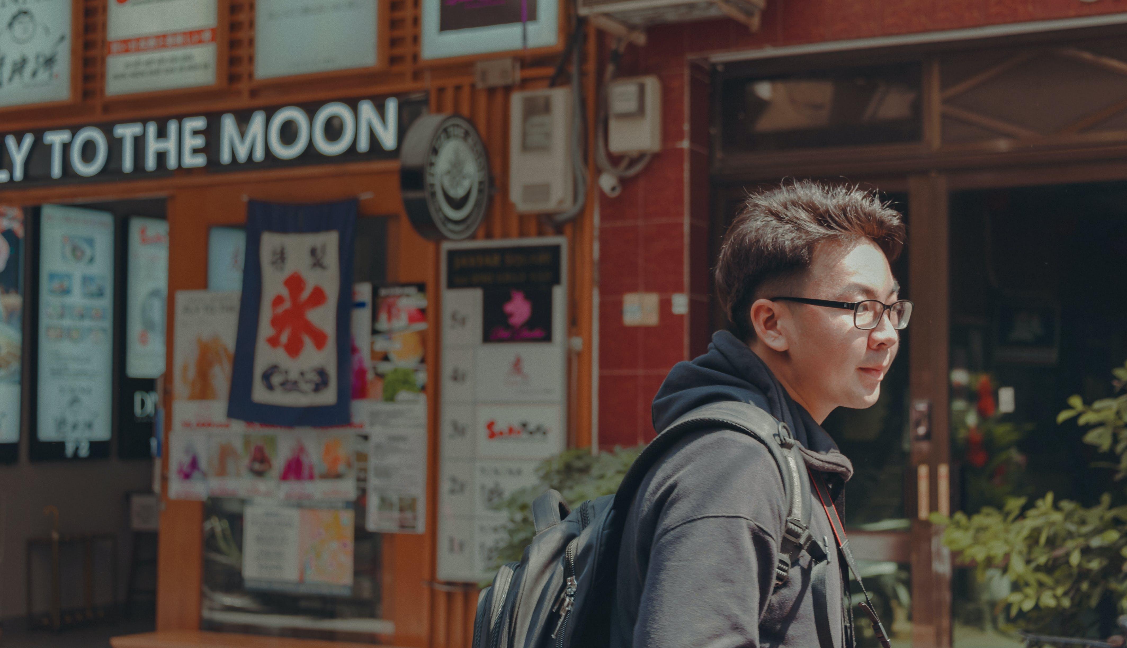 Man With Eyeglasses Wearing Black Hoodie and Black Backpack