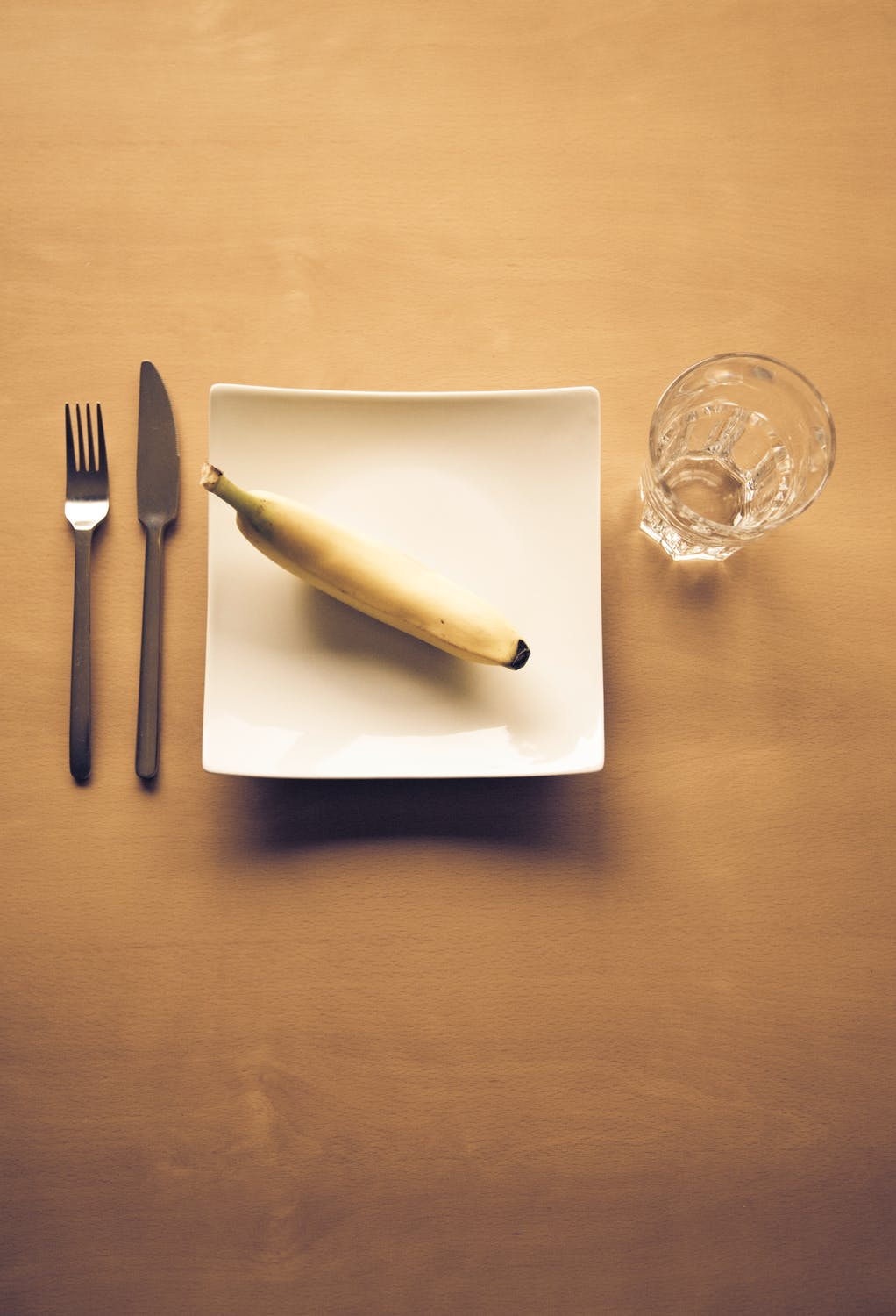 banana on a plate next to glass of water and fork and knife