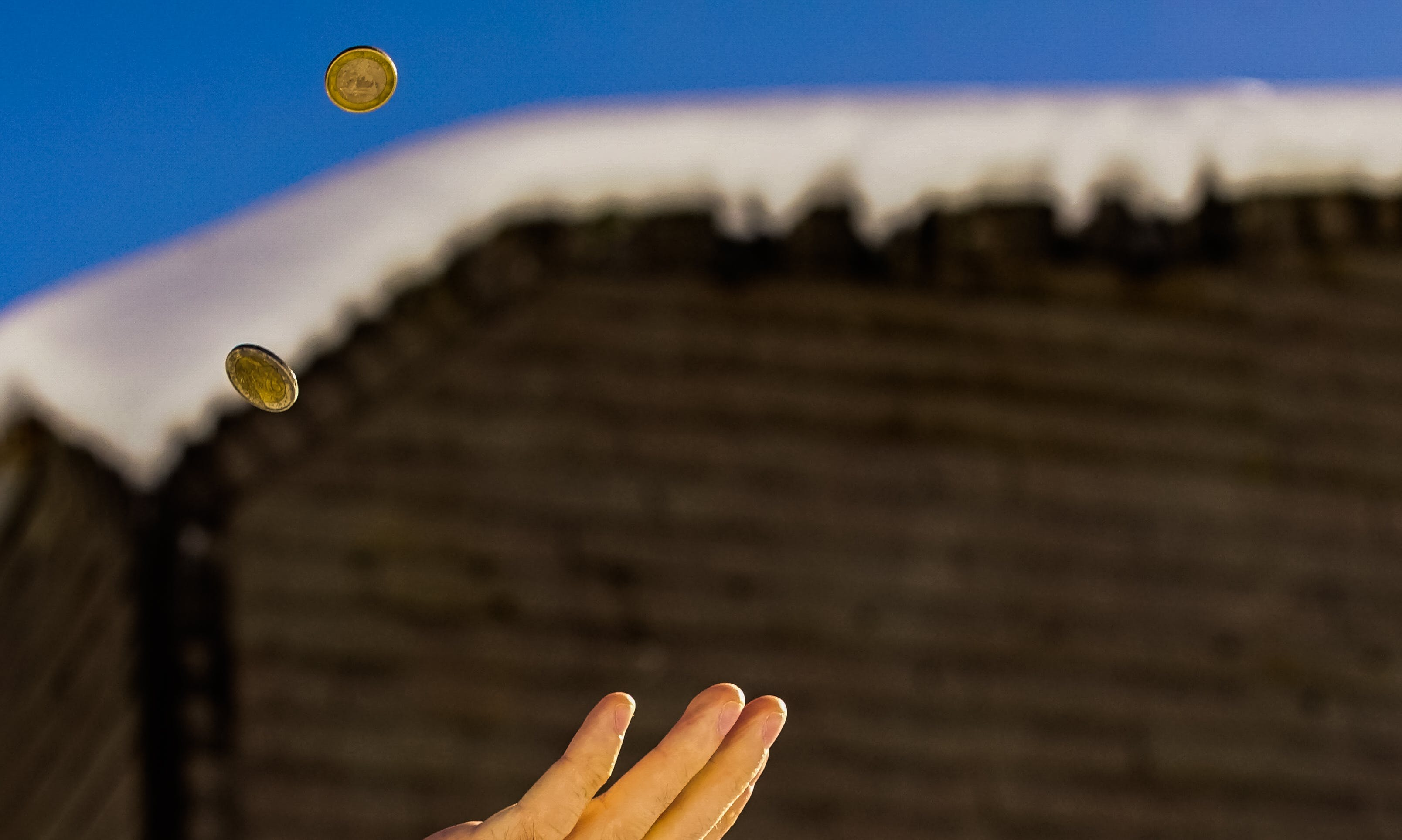 Shallow Focus Photography of Person Catching Two Gold-colored Coins
