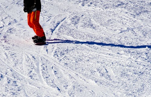 Photo of Person Wearing Black Top and Orange Pants Riding Snowboard