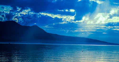 Silhouette of Mountain Near Water at Daytime