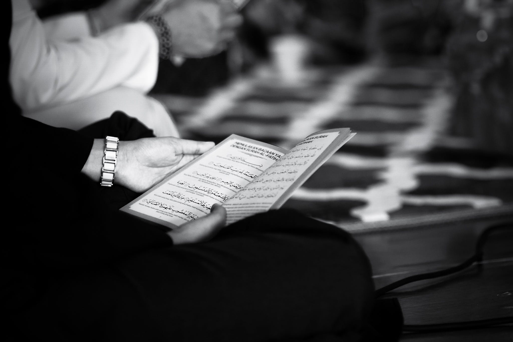 Grayscale Photography of a Person Holding Book