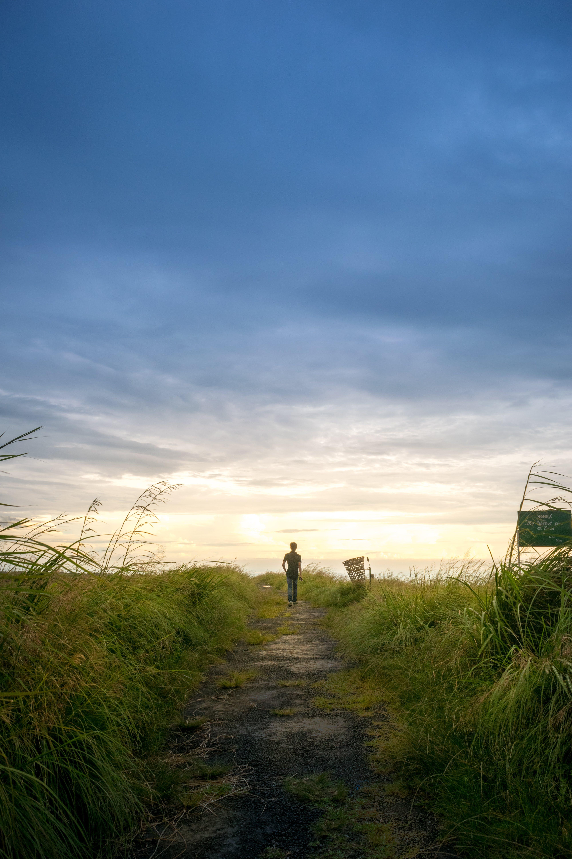 Person Wearing Black Shirt Walking Near Grass Field