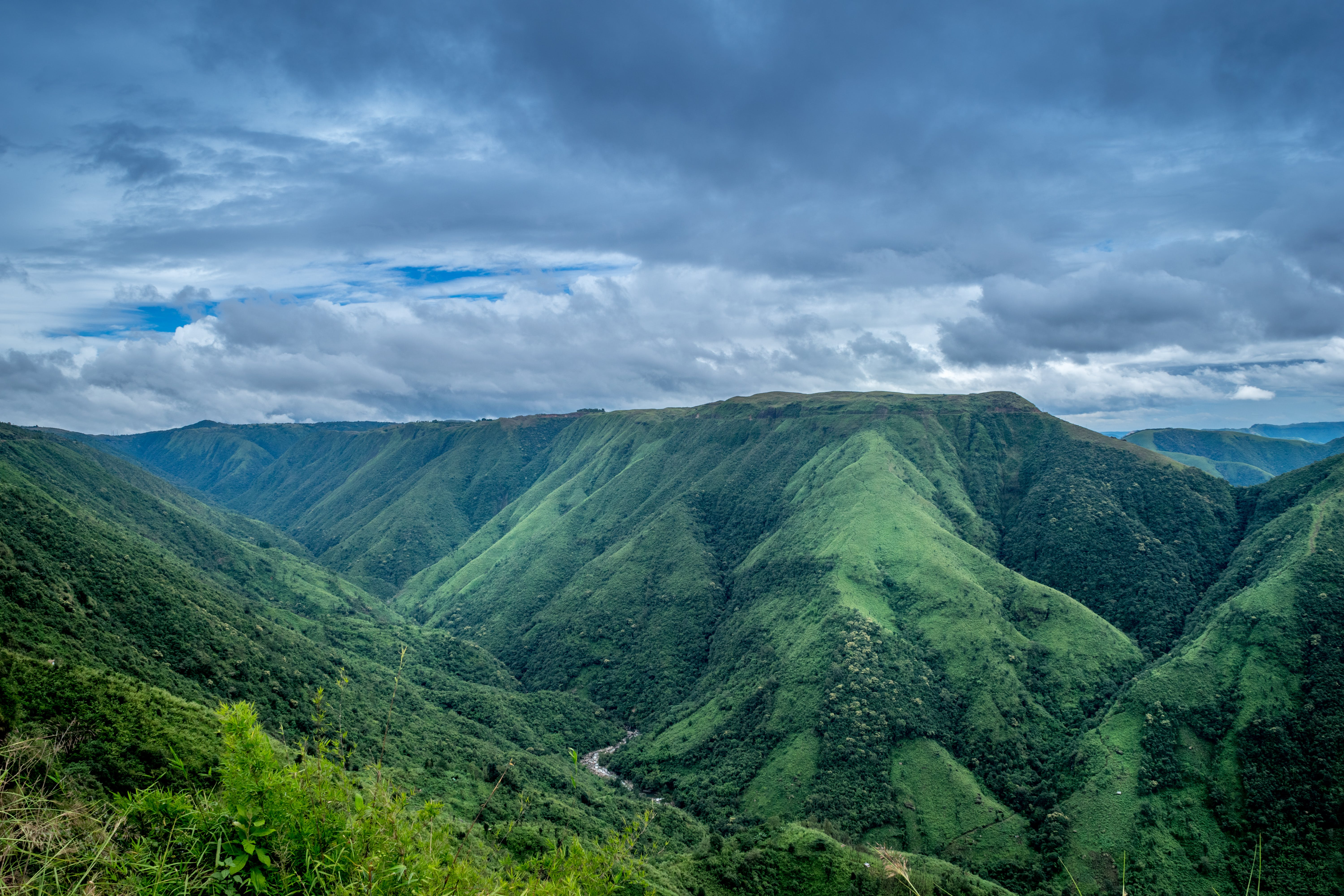 Landscape Photography of Green Mountains Under Cloudy Sky