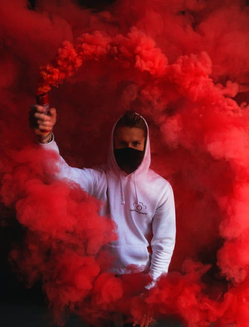 Man in White Hoodie Holding Orange Smoke