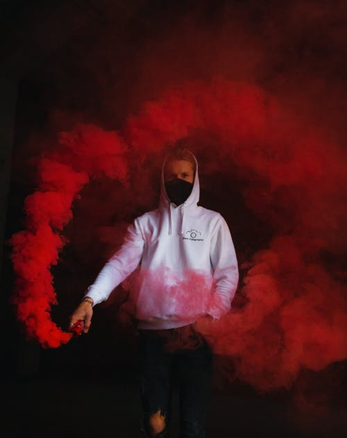 Man in White Hoodie Standing on Red Smoke