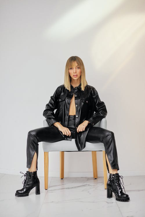 Woman in Black Leather Jacket and Black Pants Sitting on Brown Wooden Chair