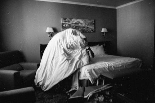 Woman in White Dress Sitting on Bed