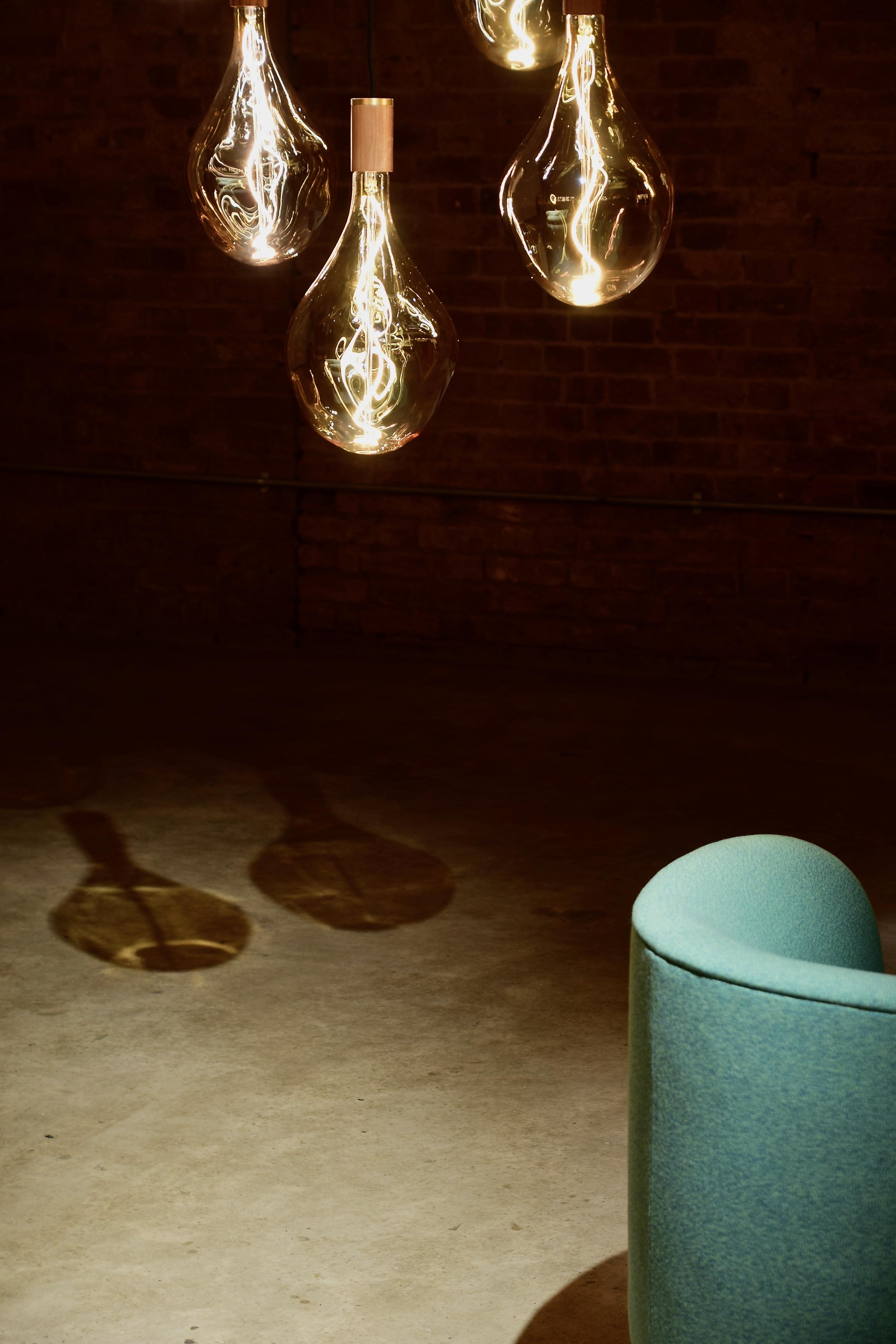 Four Hanging Light Bulbs Beside Chair