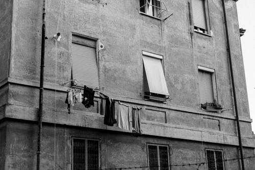 A Concrete Building of Windows with Hanging Clothes