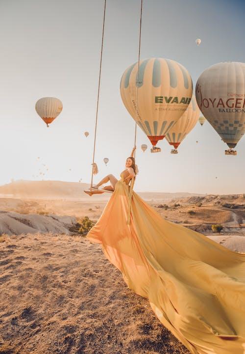 Woman in Yellow Dress Standing on Desert