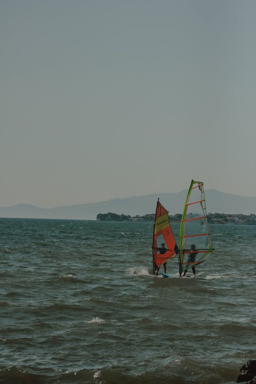 Two People Windsurfing on the Sea