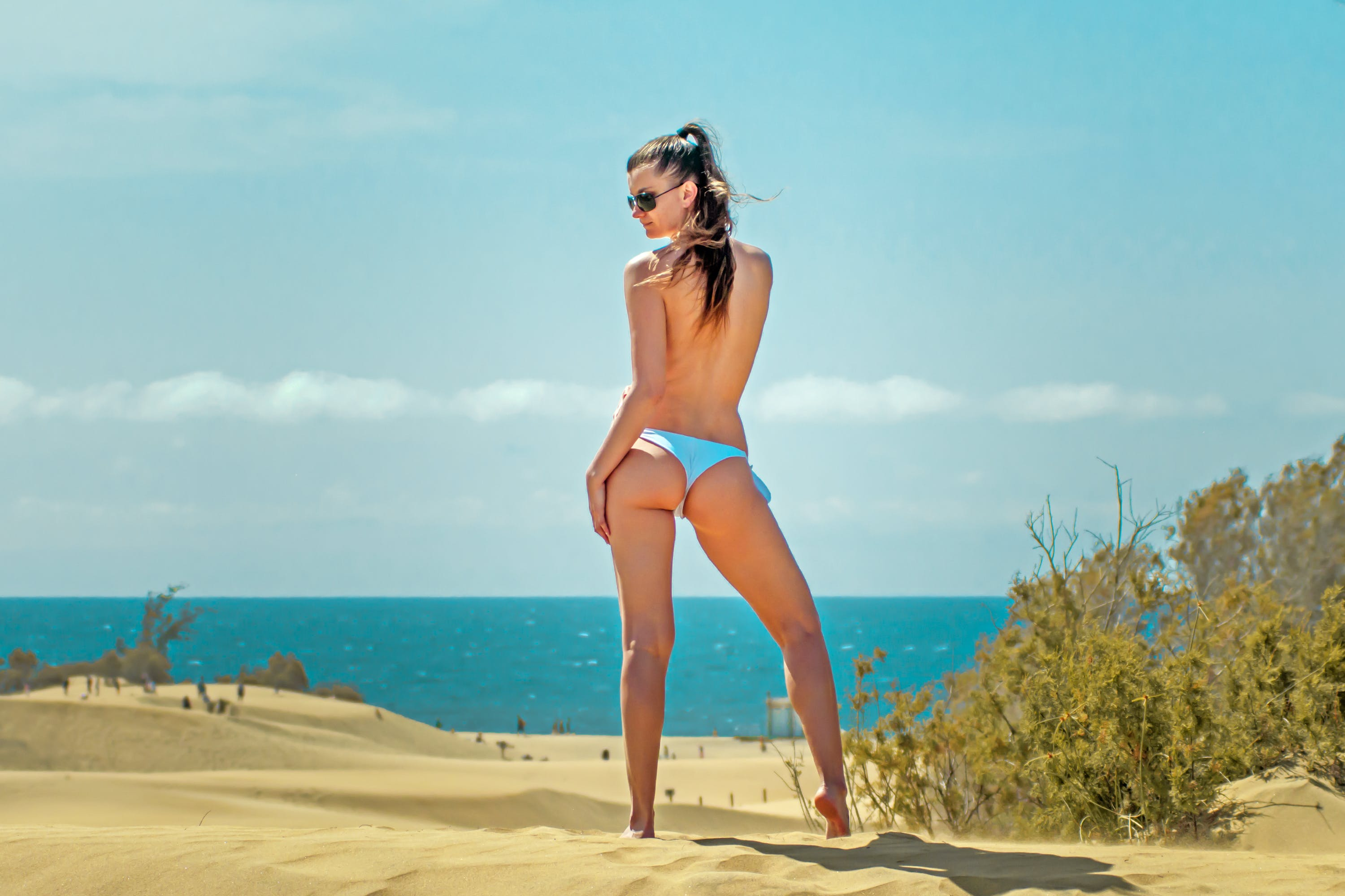 Topless Woman Wearing Blue Pantie Standing on White Sand