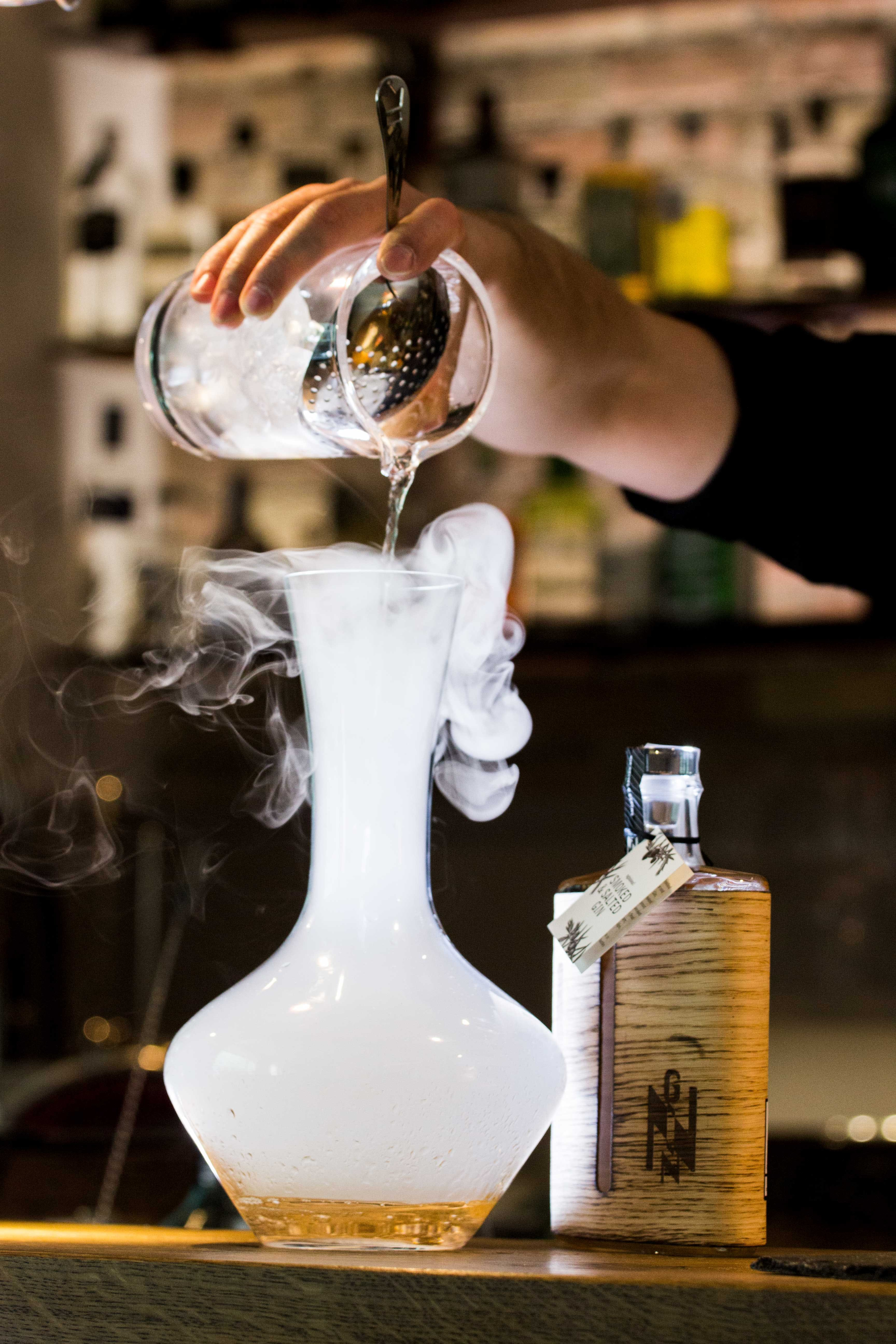 Person Pouring Liquid Into Smoking Glass Container