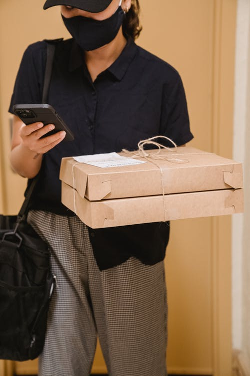 A Delivery Woman Checking Her Cellphone