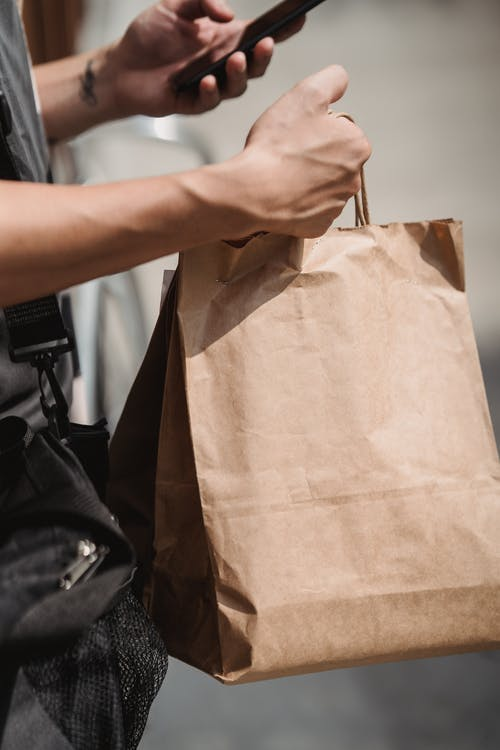 A Person Holding a Phone and Shopping Bags