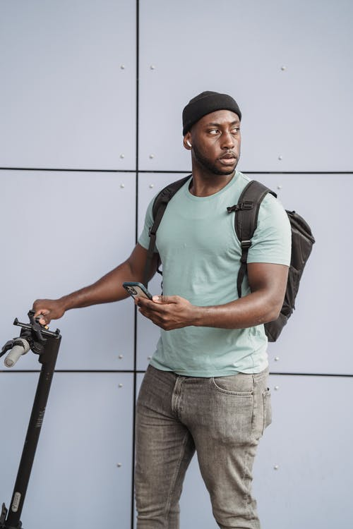 Man in Green Crew Neck T-shirt and Gray Denim Jeans Holding Black and Gray Bicycle