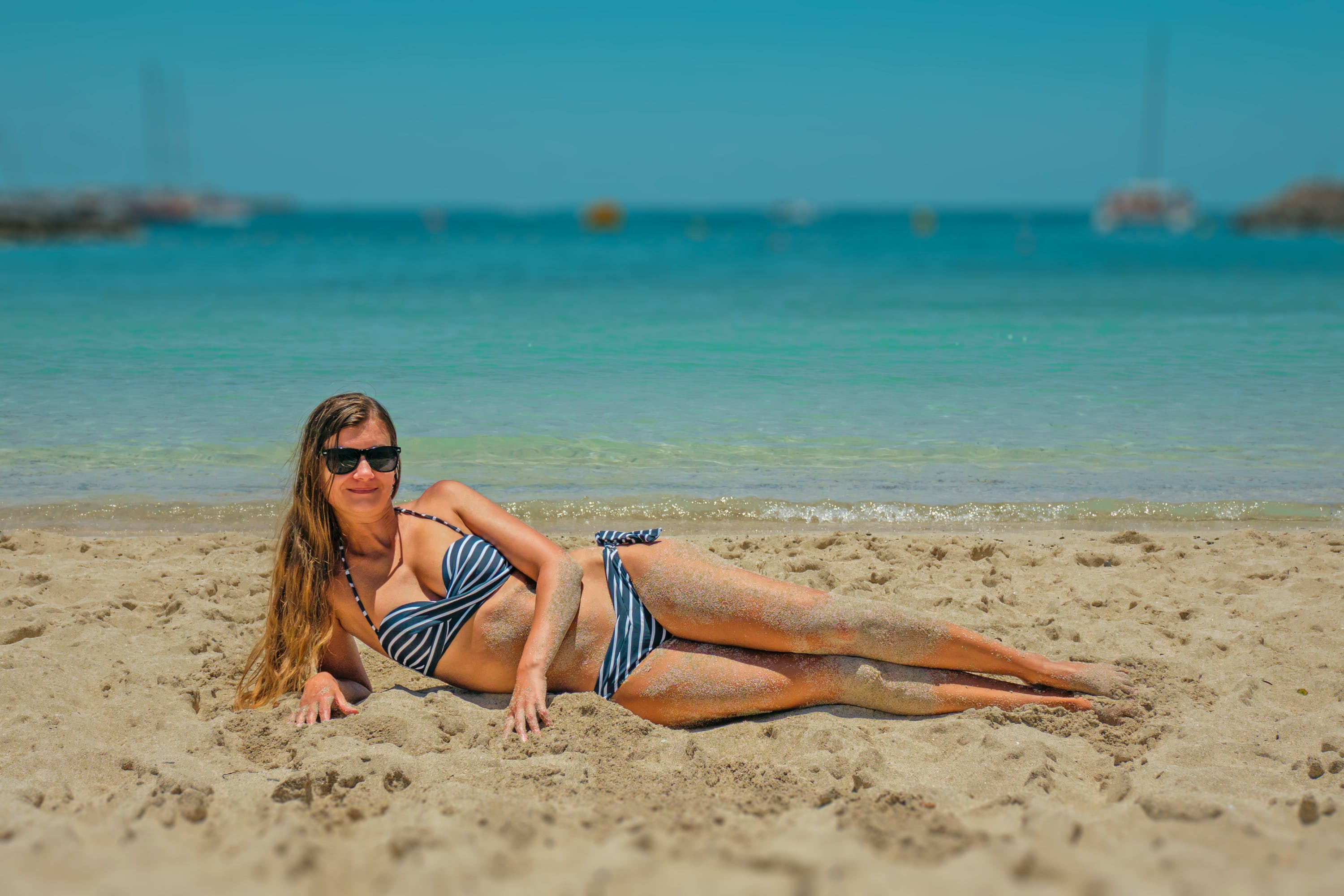 Woman in Blue and Black Bikini Lying on Beach Sand