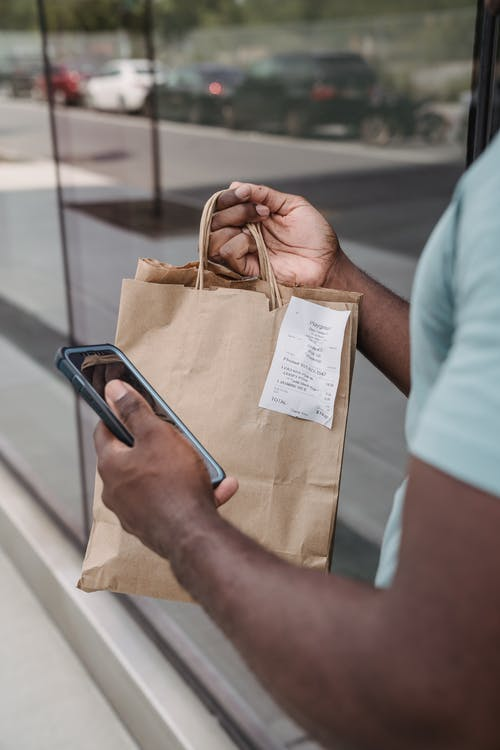A Person Holding a Shopping Bag and a Cellphone